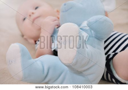 Close Up Of Blue Bear Toy Near Newborn Baby Boy Wearing In Stripped Clothing