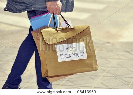 closeup of a young caucasian man with some shopping bags, one of them with the text happy black friday written in it, outdoors