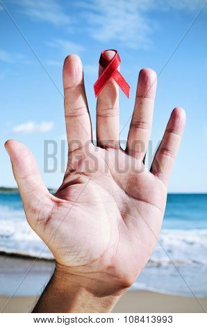 closeup of the hand of a young caucasian man with a red ribbon for the fight against AIDS in one of his fingers, near the ocean