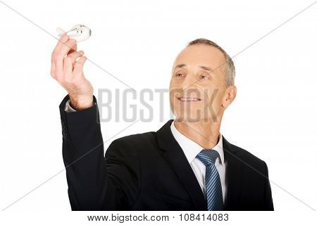 Portrait of businessman holding small airplane.