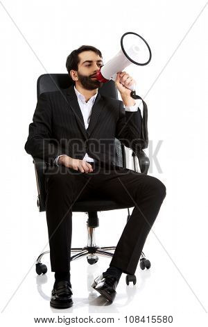 Young businessman sitting and shouting in megaphone.