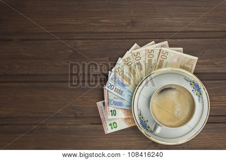Cup of coffee and money. Valid banknotes on a wooden table.