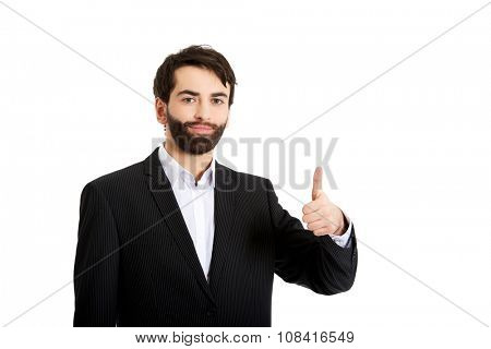 Happy smiling businessman with thumbs up gesture.