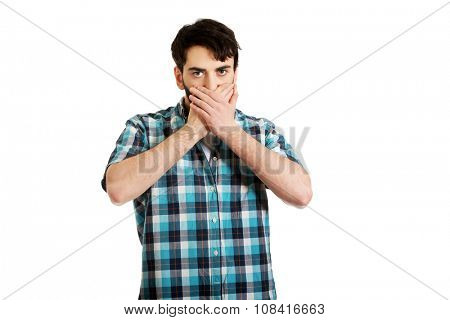 Young handsome shocked man covering his mouth.