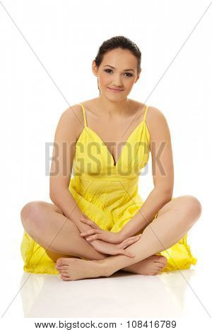 Beautiful woman sitting cross legged in yellow summer dress.