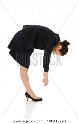 Young business woman bending down and looking.