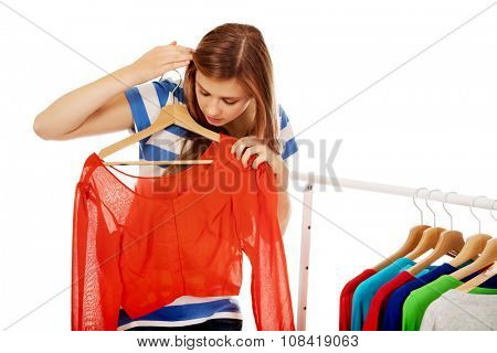Teenage woman thinking what to dress.