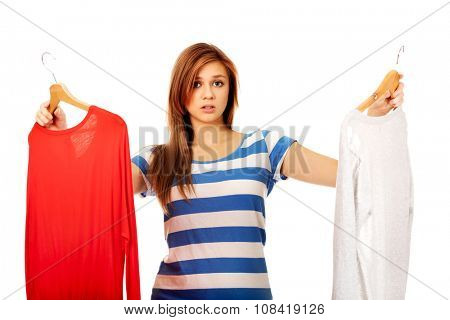 Teenage woman with two shirts thinking what to dress.
