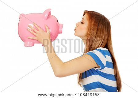 Happy teenage woman kissing a piggybank.