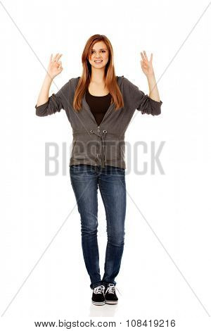 Teenage woman showing two OK signs.