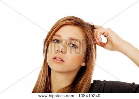 Pensive teenage woman scratching her head.