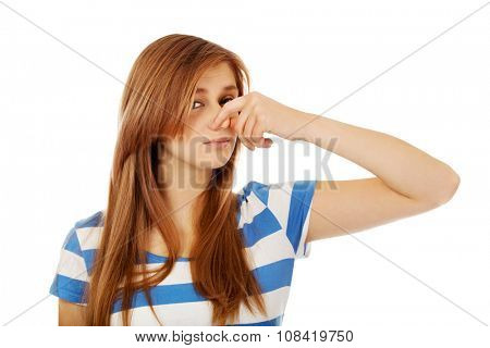 Teenage woman holding her nose because of a bad smell.