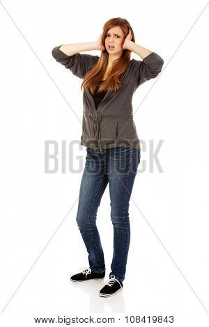 Angry teenage woman covering ears with hands.