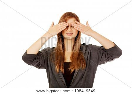 Teenage woman covering her eyes with both hands.