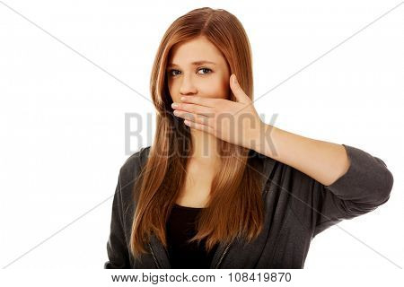Teen woman covering her mouth with hand.