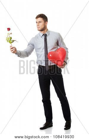 Young happy man with red rose and heart balloon.