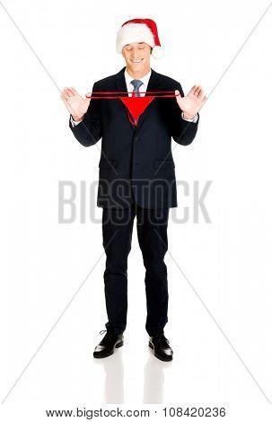 Full length santa businessman holding female thongs.