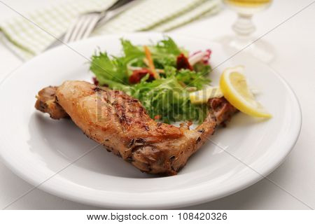 Roasted rabbit leg with salad and thyme on a plate