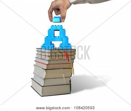 Hand Holding Block Completing Letter A Blocks On Stack Books