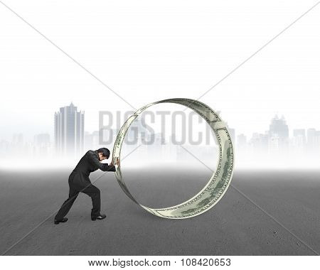 Businessman Pushing A Roll Of Dollar Bills