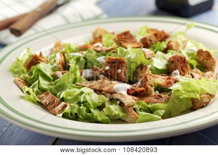 Caesar salad with lettuce, croutons, turkey meat, and mayonnaise