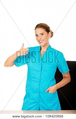 Young smile female doctor or nurse standing behind the desk and swhows thumb up.