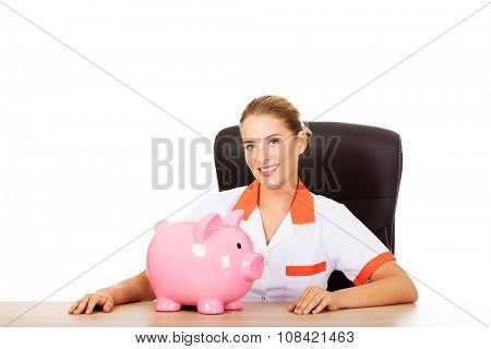 Young smile female doctor or nurse sitting behind the desk and holding a piggybank.