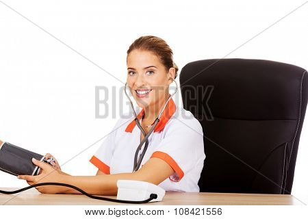 Young smile female doctor or nurse checking blood pressure patient.