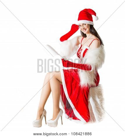 Beautiful young woman in Santa Clause costume reading Xmas letter. Christmas background