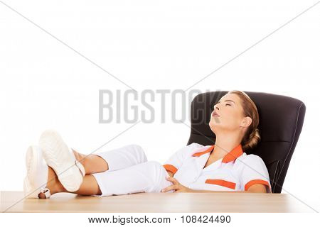 Young tired female doctor sleeping with legs on the desk.