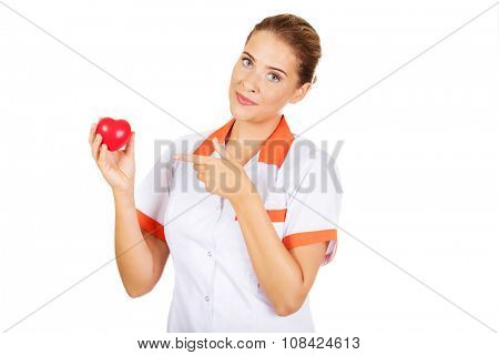 Young female doctor or nurse holding a toy heart and pointing at them.