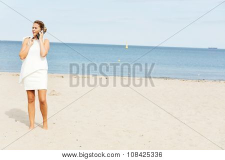Young elegant beautiful woman talking on the phone on the beach.