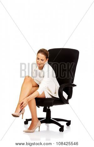 Businesswoman with leg pain sitting on the armchair.