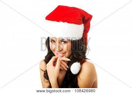 Woman shirtless with santa claus hat looking at camera.