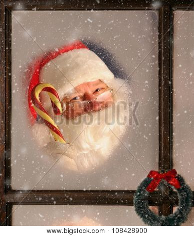 Santa Claus seen through a frosted window holding up a large old fashioned candy cane. It is snowing outside.