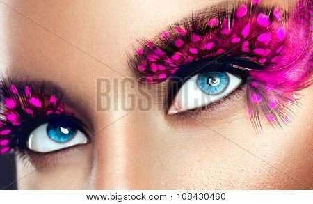 Creative Makeup. False long purple eyelashes closeup. Beauty model woman face make-up with fantasy bright eyelash