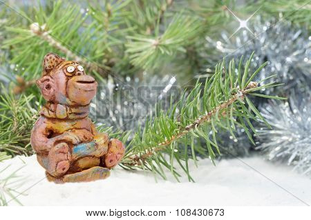 merry monkey from clay pottery sits on sled near the tree in the snow