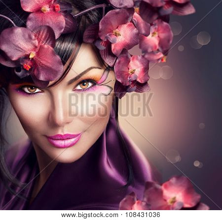Beautiful Woman with Orchid flower hairstyle and creative makeup. Beauty brunette lady portrait with holiday make-up