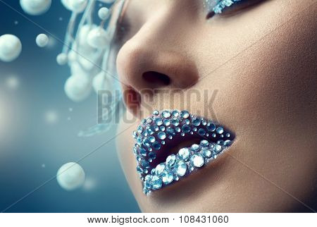 Winter model Woman makeup. Creative Christmas Girl Make up. Holiday Make-up with gems on lips. Snow Queen High Fashion Portrait over Blue Snow Background. Eyeshadows, False Eyelashes and Crystals