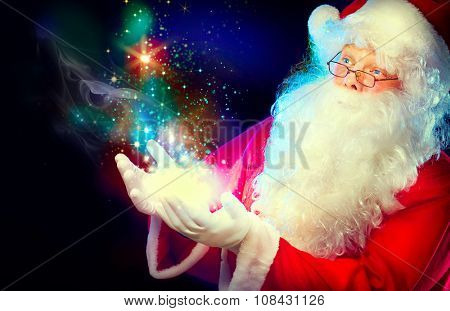 Santa Claus with magic gift in his hands. Portrait of happy Santa Claus making magic at night