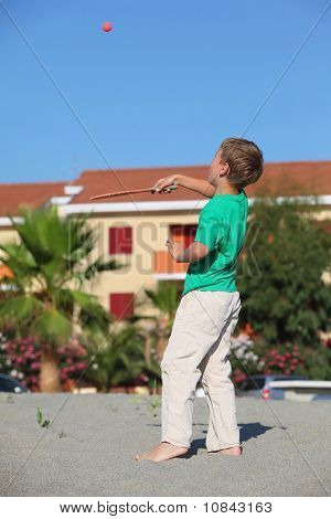 Boy Tosses Up  Tennis Ball  Racket, Upright On Sand By  Sun Day On Rest