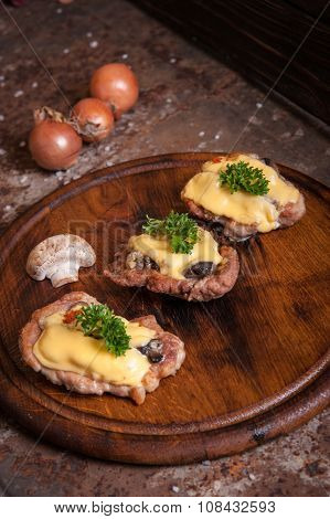 Meat patties with mushrooms and cheese, decorated with greenery