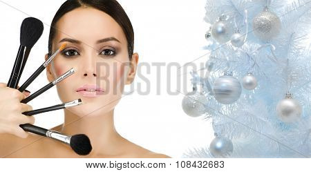 portrait of attractive  caucasian woman brunette isolated on white studio shot face closeup makeup brushes christmas new year tree