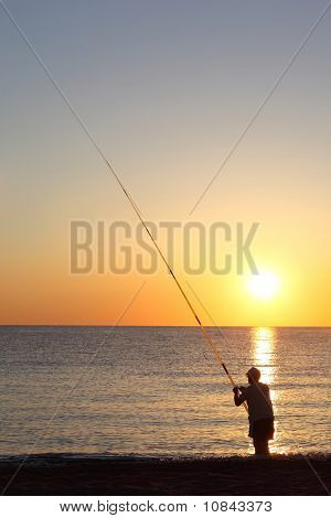 Fisherman Stands Ashore Exterminating With  Large Fishing-rod