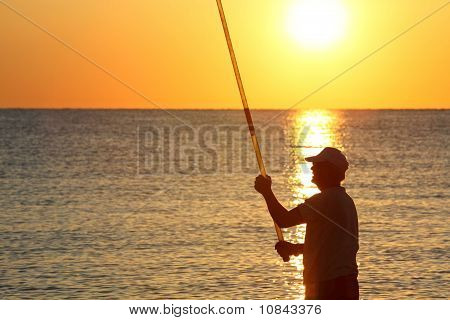 Man Stands Ashore With Fishing-rod And Fishes On Sunset