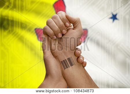 Barcode Id Number On Wrist Of Dark Skin Person And Canadian Province Flag On Background - Nunavut