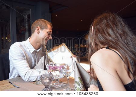 Couple In Love Looking At The Menu For Dinner