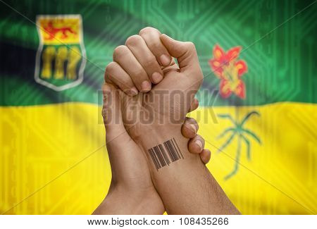 Barcode Id Number On Wrist Of Dark Skin Person And Canadian Province Flag On Background - Saskatchew
