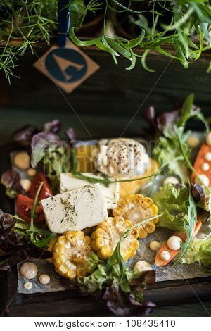 Baked vegetables: corn, carrots, greens and cheese with cream cheese on a plate