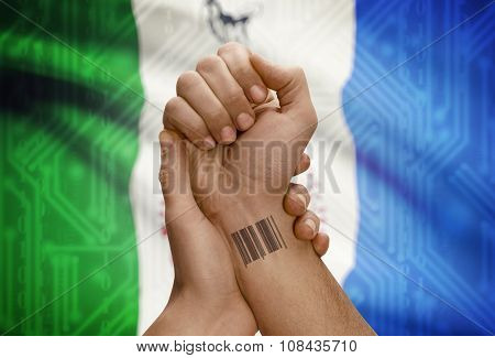 Barcode Id Number On Wrist Of Dark Skin Person And Canadian Province Flag On Background - Yukon